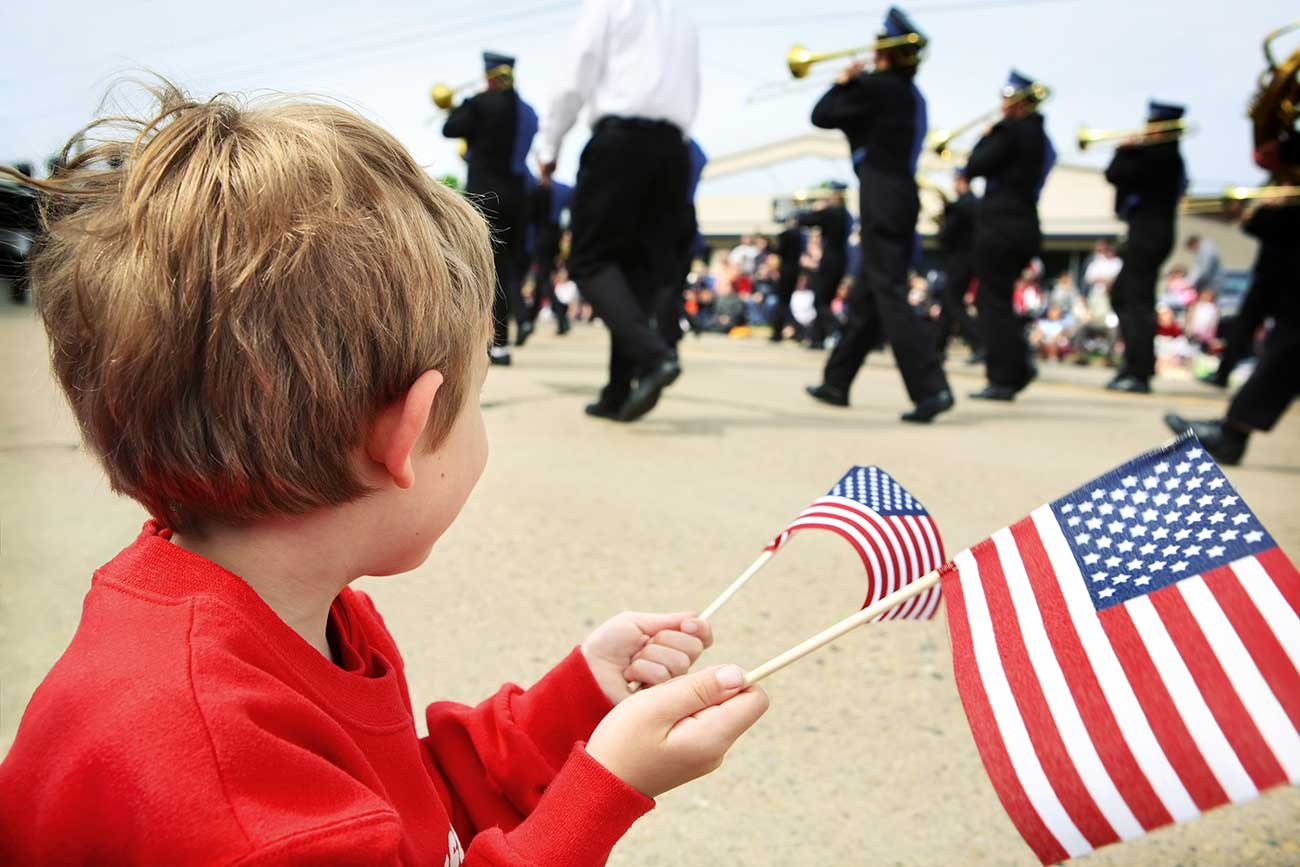 young boy holding American flags during parade