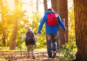 father and son hiking in woods